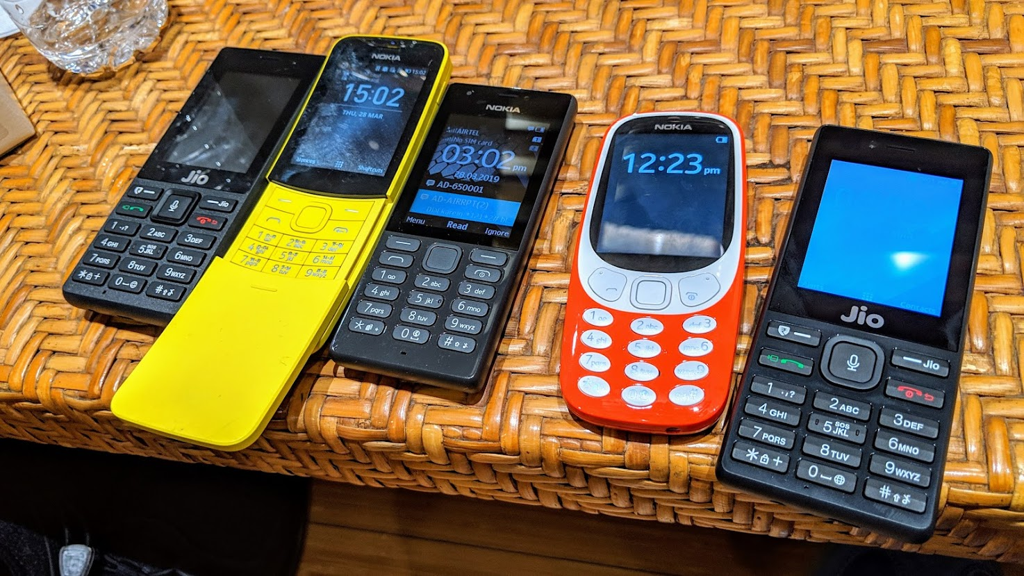 Many types of phones on a table.